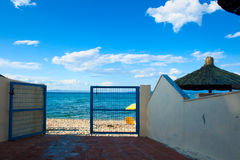 Way to the beach. Gate to the beach at sunny day. Dark road to light sand. Beach umbrellas, blue water and sky royalty free stock image