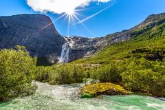 Way to Briksdal glacier, waterfall in Norway. Waterfall, river and green trees on the way to Briksdal or Briksdalsbreen glacier in Olden, Norway royalty free stock photos