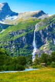 Way to Briksdal glacier, waterfall in Norway. Waterfall, river and green trees on the way to Briksdal or Briksdalsbreen glacier in Olden, Norway stock image