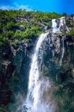 Way to Briksdal glacier, waterfall in Norway. Waterfall and green trees on the way to Briksdal or Briksdalsbreen glacier in Olden, Norway stock photography