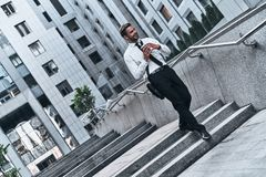 On the way to business meeting. Full length of young man in full suit smiling while walking outdoors royalty free stock photo