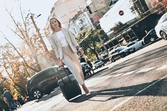 On the way to business meeting. Full length of young woman in suit pulling luggage while walking outdoors royalty free stock images