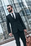 On the way to business meeting. Good looking young man in full suit and sunglasses carrying fashionable bag and looking away while standing outdoors Royalty Free Stock Photo