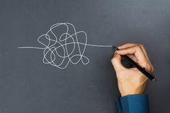 The way to business thinking success concept. A businessman hand drawing a white tangle line on blackboard