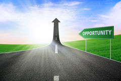 The way to gain opportunity. A road turning into an arrow rising upward with a road sign of opportunity, symbolizing the way to gain opportunity Stock Photo