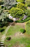The way to the garden. Walk way to the green garden ,a stone path direct throw the garden Stock Photography