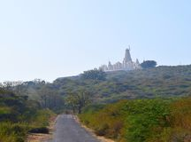 Way to God - A Jain Temple on Hill and a Road - Hastagiri, India. This is a photograph of a Jain temple located high on hill, at Hastagiri, Gujarat, India stock photo