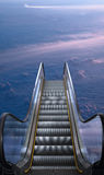 Way to heaven. Electric escalator with clouds in the background Stock Image