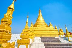 The golden stupa in Kuthodaw Pagoda complex, Mandalay, Myanmar. The way to the huge golden Kuthodaw Pagoda decorated with small golden spires with Hti umbrellas stock photography