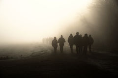 Way to light. Persons are going into the fog Royalty Free Stock Photo