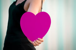 On the way to love. Young female walking out of the frame and boldly holding out a large magenta heart Stock Images