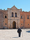 The way to the monastery. RETHYMNO, GREECE - OCTOBER 15, 2013: The old man with a cane goes to the entrance (Western Door) of Arkadi Monastery, also called Royalty Free Stock Photography