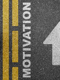 Way to motivation. An asphalt road with the text 'motivation' painted on the surface Royalty Free Stock Photos