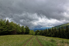 Way to from mountain top with green meadows in the rain clouds Stock Photo