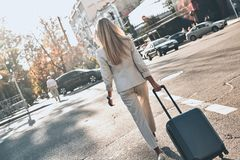 On the way to new opportunities. Rear view of young woman in suit pulling luggage while walking outdoors stock photo