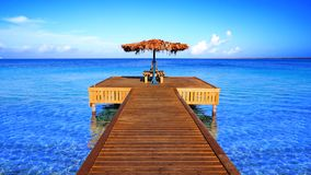 Way to paradise. Wooden dive pier in beautiful turquoise water in the Caribbean stock photo