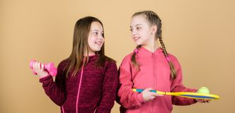 On the way to perfect shape. Happy children with sport equipment. gym workout of teen girls. Tennis racket and ball for. Activity. Little girl. Fitness barbell stock photos