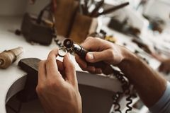 On the way to perfection. Close-up of male jeweler`s hands polishing silver ring at his jewelry making studio. Jewelry making workshop. Master`s hands stock photos