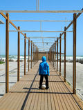 Way to play. Boy walking through a wooden structure,going to the beach to play football Stock Images