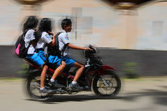 On a way to school. RANTEPAO, INDONESIA - JULY 20: Three teenage students riding a motorcycle on Sulawesi July 20, 2011 in Rantepao, Indonesia Royalty Free Stock Image