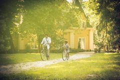 Way to school. African American father and daughter driving bike trough park royalty free stock photo