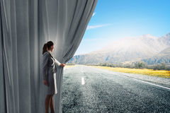 Way to something new. Businesswoman opening curtain to new roads and opportunities Stock Photography