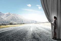 Way to something new. Businesswoman opening curtain to new roads and opportunities Royalty Free Stock Images