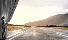 Way to something new. Businesswoman opening curtain to new roads and opportunities Stock Images