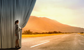 Way to something new. Businesswoman opening curtain to new roads and opportunities Royalty Free Stock Photography