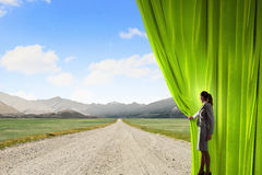 Way to something new. Businesswoman opening curtain to new roads and opportunities Stock Image