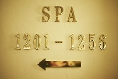 Way to spa. Hotel room numbers and the golden arrow showing the way to the spa in a fancy luxury hotel stock photos