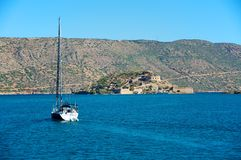 Way to Spinalonga. Through the waves of blue, the Mediterranean Sea, a small yacht sailing ahead. Its purpose is seen already on the horizon. A small island with Stock Photo