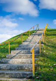 Way to success. Steep stairs leading up a hill outdoor into the blue sky Stock Photos