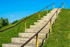 Way to success. Outdoor stairs up onto a green hill into the blue sky Stock Image