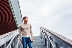 Way to Success. American Graduate Student studying in New York, wearing collarless knit sweater, holding laptop computer, standing on stairs on campus, looking Royalty Free Stock Photography
