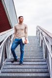 Way to Success. American Graduate Student studying in New York, wearing collarless knit sweater, jeans, sneakers, holding laptop computer, standing on stairs Stock Photos