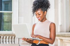 Way to Success. Young African American woman with afro hairstyle wearing sleeveless light color top, standing in vintage office stock photography