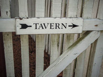This Way to the Tavern. Old wooden Tavern sign on a wooden fence Stock Photography