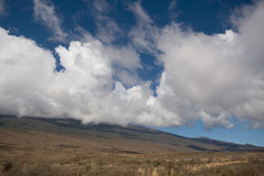On way to top. Clouds climbing hillside of Mauna Kea at lower elevation, Big Island, Hawaii Stock Image