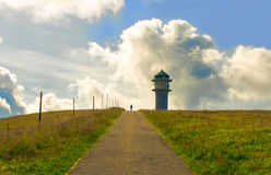 Way to a tower in the green grass and clouds on mountain. Royalty Free Stock Photos