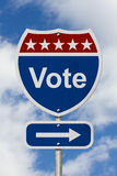 Way to Vote Road Sign. Red, white and blue American highway sign with word Vote with sky background Stock Images