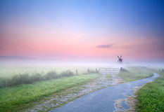 Way to windmill in morning fog Stock Photography