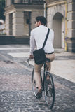 On the way to work. Rear view of young man in glasses looking away while riding his bicycle Stock Image