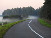 Road, trees and fog in morning, Lithuania stock photo