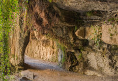 Way under the rocks. At the monastery of Sant Miquel del Fai in northeastern Catalonia,  the way has been cut through the rocks forming a short tunnel Stock Images