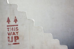 This Way Up. Detail of an old white stairway with the phrase This Way Up painted in red Stock Photography
