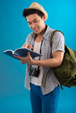This way!. Vertical image of a young man with a map-book reading it with interest isolated on a blue background Royalty Free Stock Photography