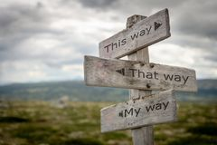 This way, that way, my way wooden signpost with black arrows in landscape scenery. royalty free stock photo