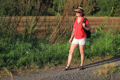 On the way. Woman with hat and backpack standing on the road in countryside Stock Image