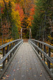 This is the Way. A wooden foot bridge crosses a river into a forest full of glorious fall colors in the White Mountains of New Hampshire royalty free stock photo